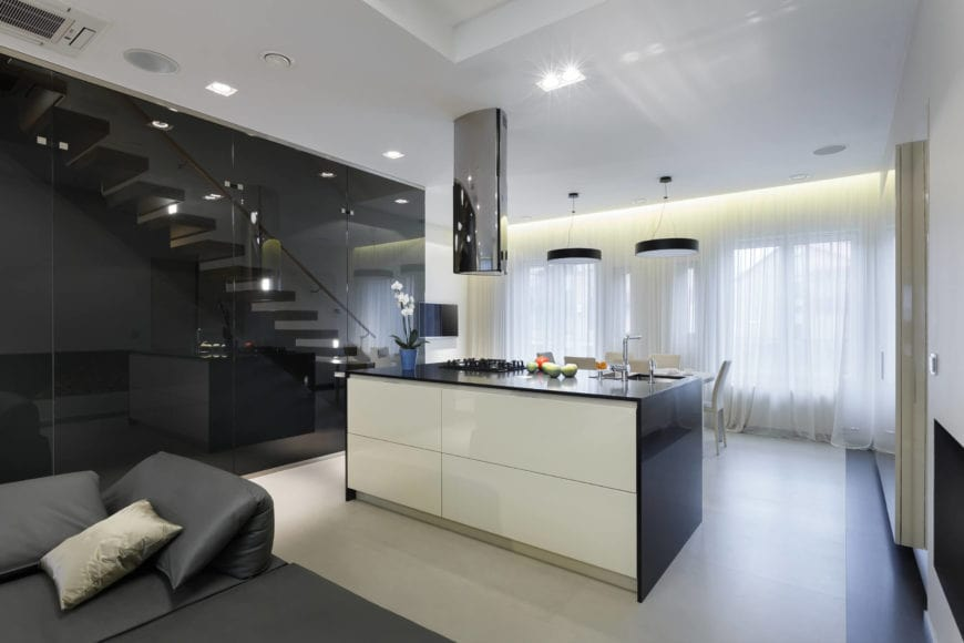A very simple yet sleek kitchen with a minimalist kitchen bar over tiled flooring. It is fitted with a sink and cooktop that's complemented by a mirrored vent hood matching with the floor to ceiling cabinets.