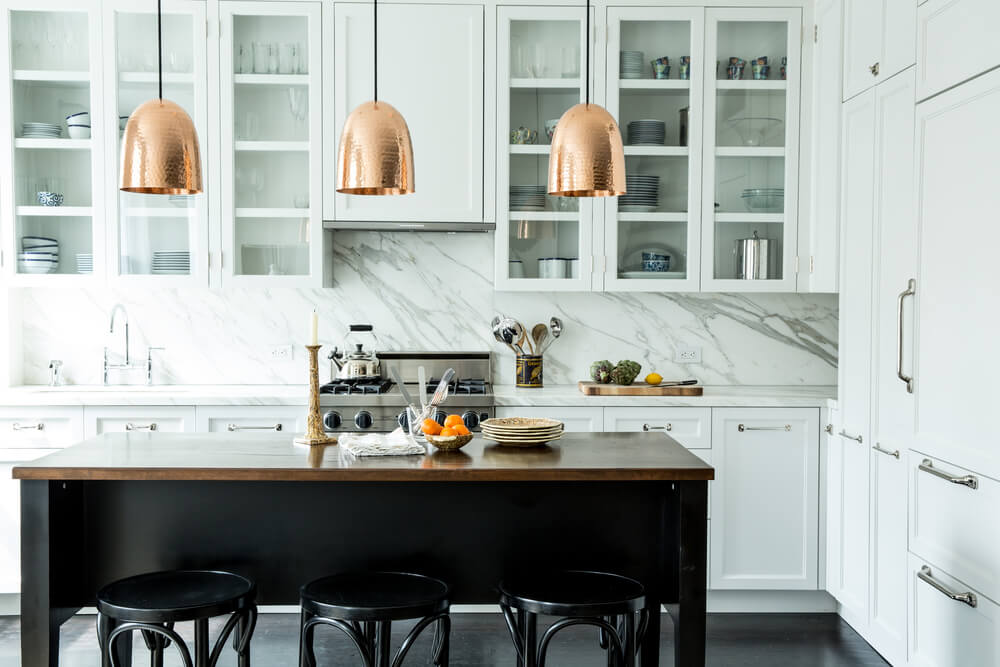 This kitchen offers white and glass front cabinets contrasted by a dark wood island bar that's lined by copper dome pendants and black bar stools. Marble backsplash provides a classy design to the area.