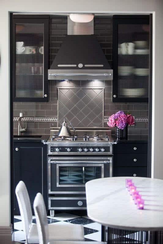 A small kitchen with a vintage vibe featuring a cooking range and glass front cabinets flanking a gray vent hood. It has black cabinets and an undermount sink placed against the charcoal subway tile backsplash.