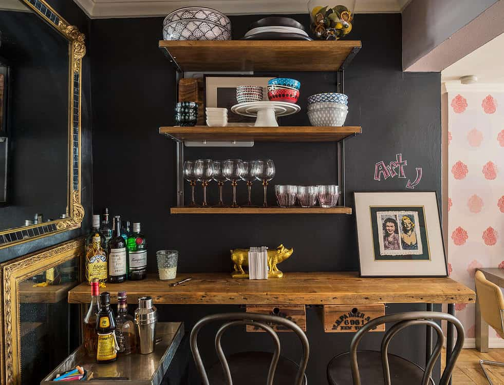 This kitchen is styled with vintage and industrial touches showcasing brass-framed mirrors and a wooden countertop paired with metal chairs. It includes three-tier floating shelves that are fixed against the chalkboard wall.