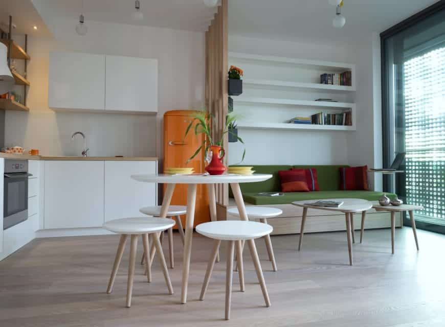 An eat-in kitchen integrated with a living space. It showcases a round dining set and a bold orange fridge that stands out against the white cabinets and walls.