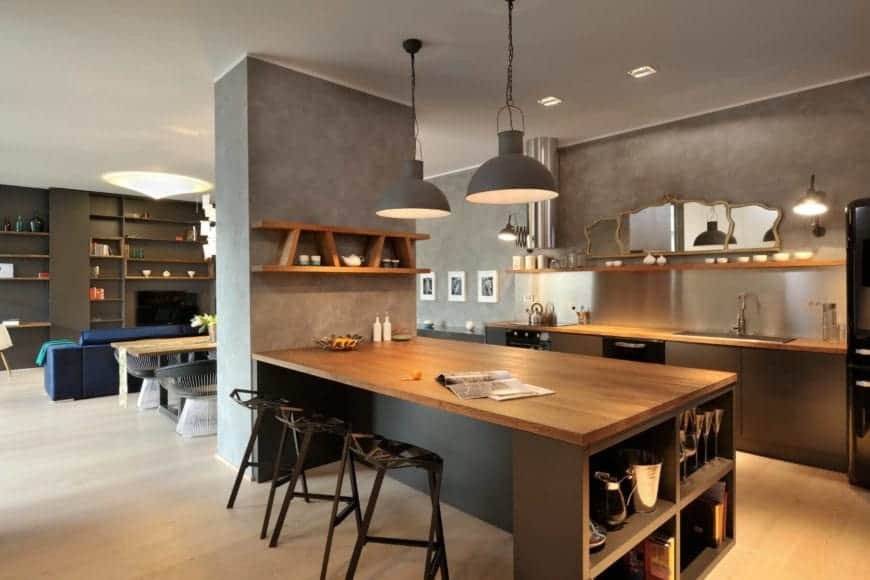 A warm and cozy kitchen decorated with a stylish mirror and gray dome pendants that hung over a wood top central bar lined with geometric stools. It has black appliances and a floating shelf fixed above the brushed aluminum backsplash.