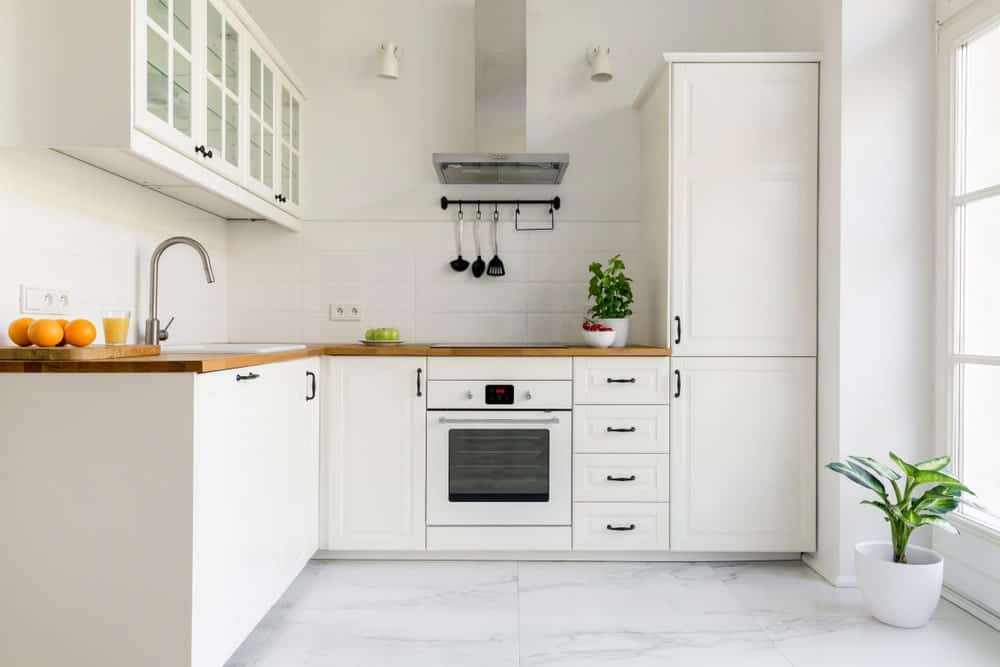 Apartment kitchen with a neutral palette showcasing white cabinets, tiled backsplash, light wood countertop, white appliances and marble tiled flooring.