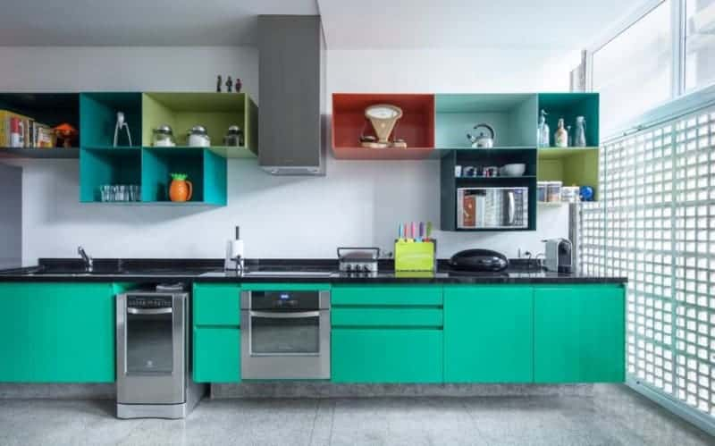 The white wall in this small kitchen is contrasted by multi-colored shelvings and green cabinets topped with a black granite countertop. The area has concrete tiled flooring and full-height windows on the side covered with a perforated panel.