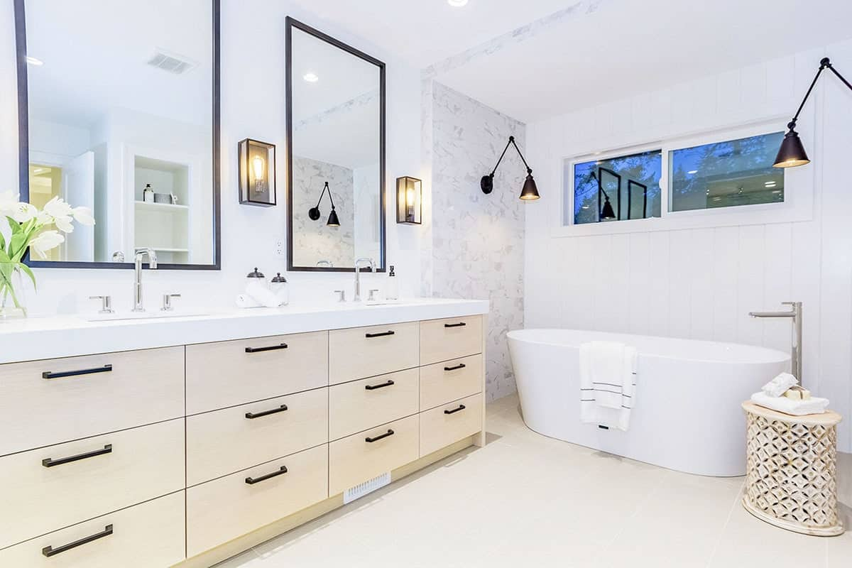 The modern master bathroom features a freestanding tub complemented by a stylish round side table. It includes various styled sconces and a dual sink vanity paired with framed mirrors.
