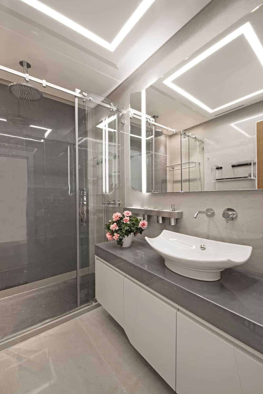 A classic master bathroom filled with a walk-in shower and a floating vanity topped by a vessel sink. It is accompanied by chrome fixtures and a frameless mirror fixed against the tiled wall.