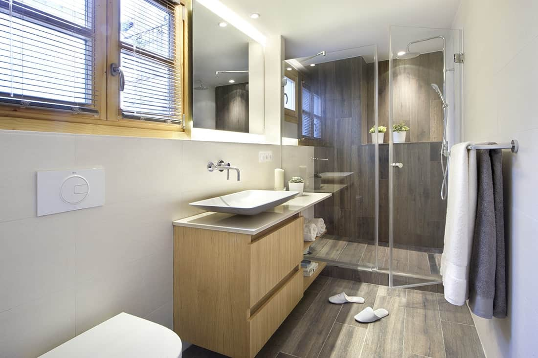 Well-lit master bedroom with a walk-in shower and a modern toilet flanking the floating vanity topped with a vessel sink. It has louvered windows and wide plank flooring that extends to the shower backsplash.