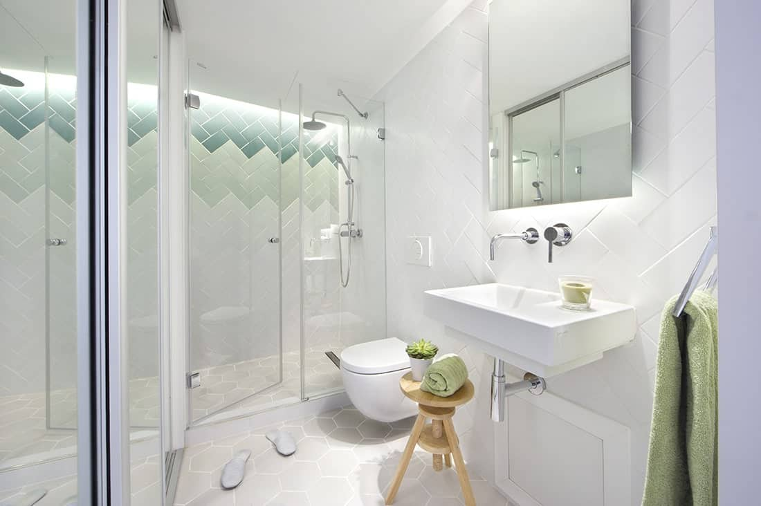 Bright master bathroom with hex tile flooring and stylish walls arranged in a herringbone pattern. The room is filled with a walk-in shower, sleek toilet and a wall-mounted sink complemented by a frameless mirror and a wooden round stool.