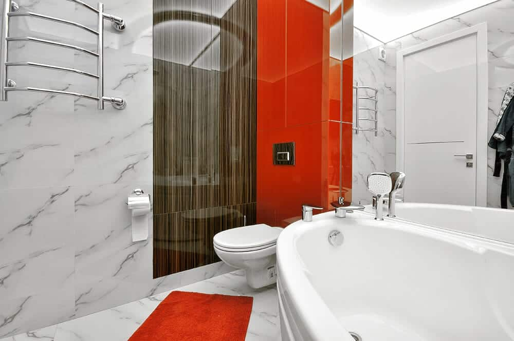 Bold red tones add a stunning contrast in this marble master bathroom. It is completed with a bit of wooden panel and a mirrored wall that create a larger visual space in the room.