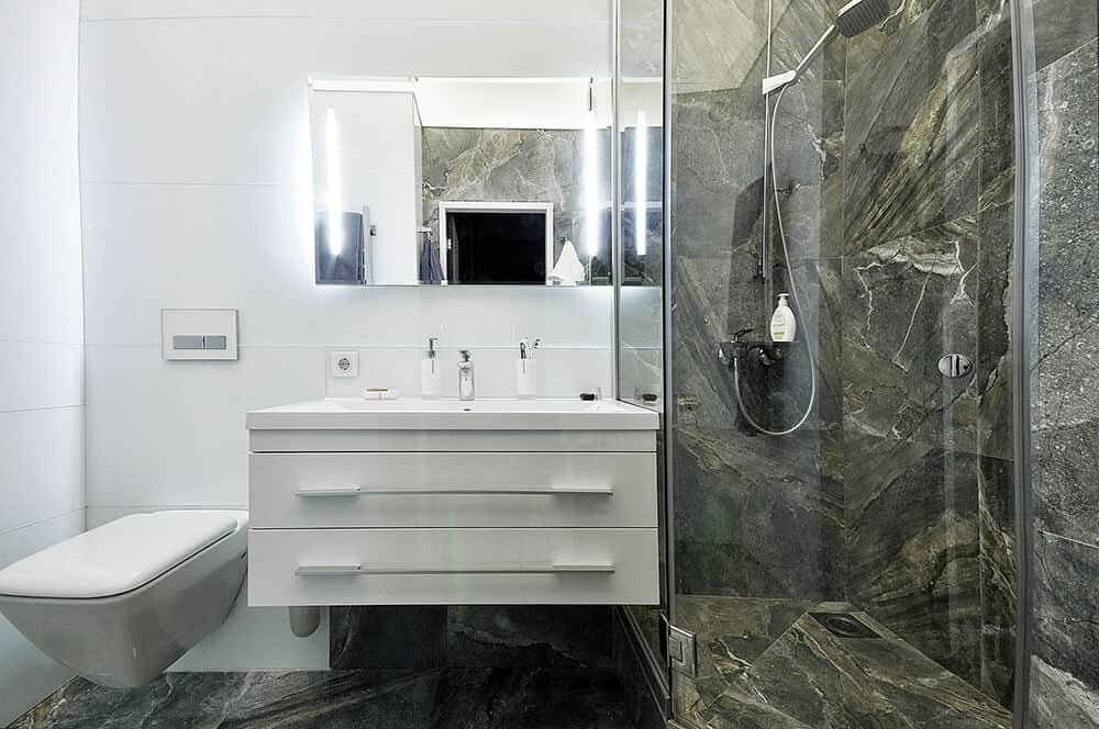 A wall-mounted toilet and a walk-in shower flanked the floating vanity in this master bathroom. The room is filled with white hues that are beautifully contrasted by natural marble flooring and backsplash.