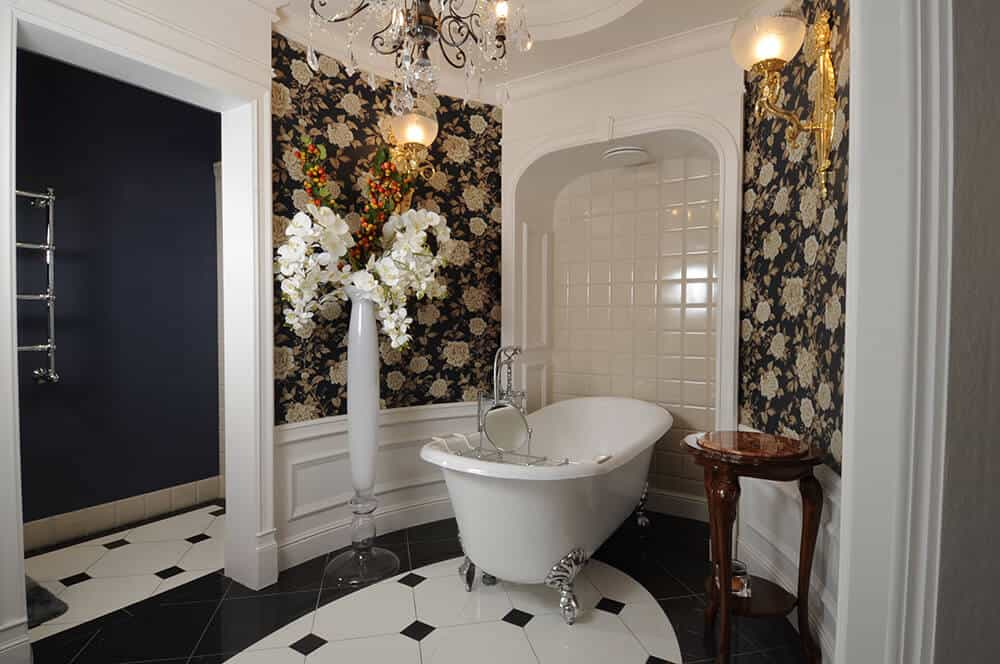Black floral wallpaper sets a classy and charming backdrop in this master bathroom with a clawfoot tub and a tall vase over tiled flooring. It is illuminated by warm sconces and a crystal chandelier that hung from the tray ceiling.