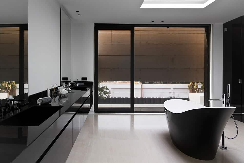 Minimalist master bathroom with floating sink vanity and a black clawfoot tub situated underneath the skylight. It has beige tiled flooring and a glass sliding door covered in a blackout shade.