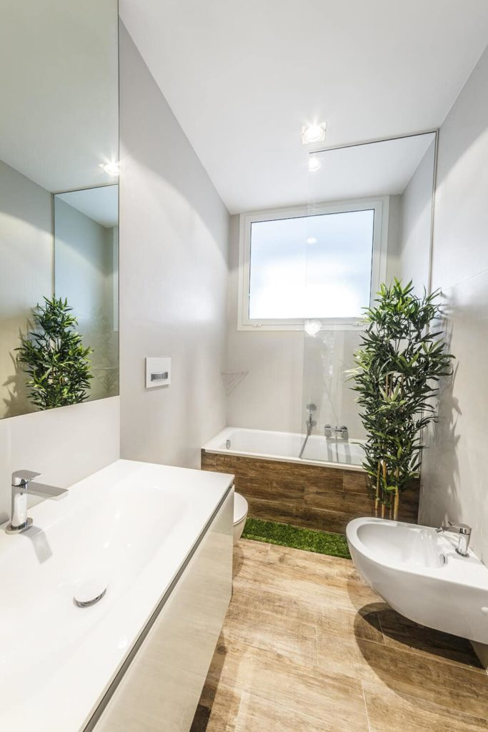 Green plants create a refreshing ambiance in this master bathroom. It is filled with a bathtub, a bidet and a large sink mounted under the frameless mirror.