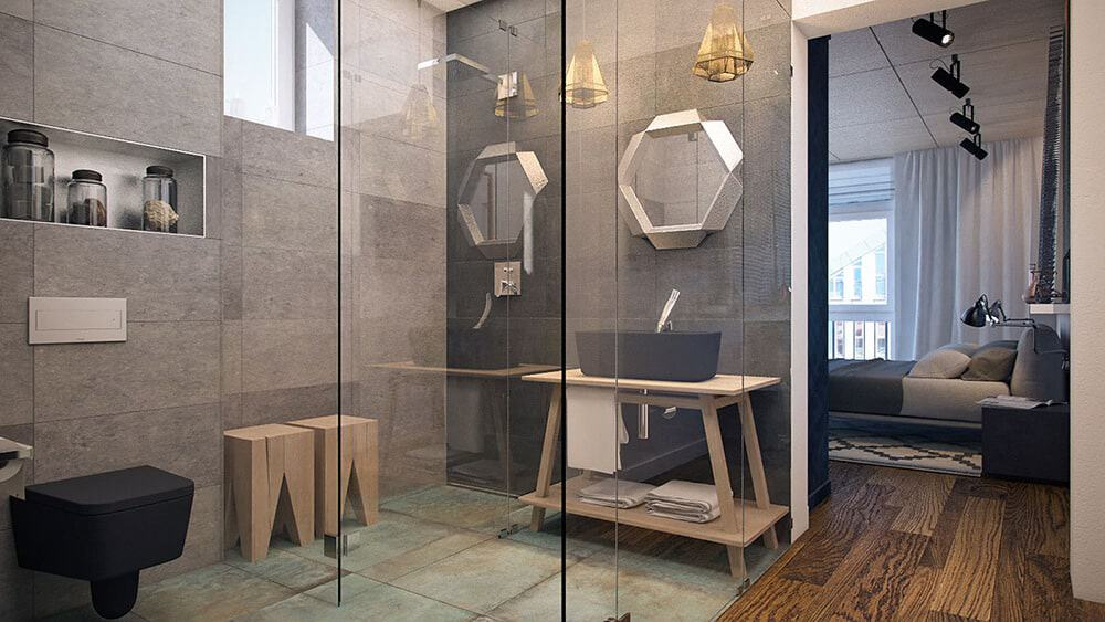 This unique master bathroom features stylish wooden stools and a black toilet that matches the vessel sink paired with a hexagonal mirror. It has distressed green flooring and gray tiled walls enclosed in frameless glass.
