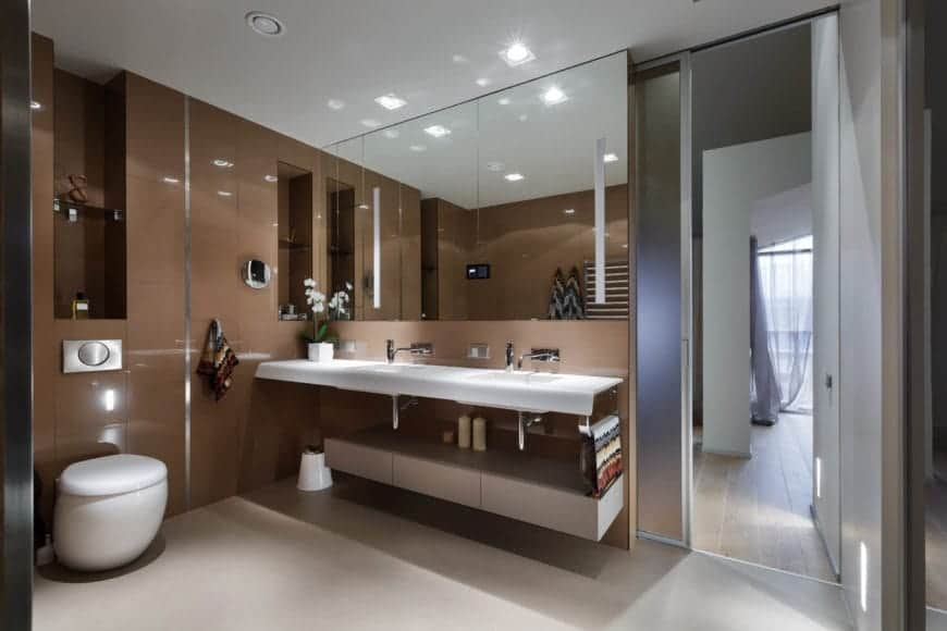 A stylish master bathroom filled with a unique toilet and a quartz countertop fitted with dual sink. It includes inset shelves and a large mirror that makes the room appear bigger.