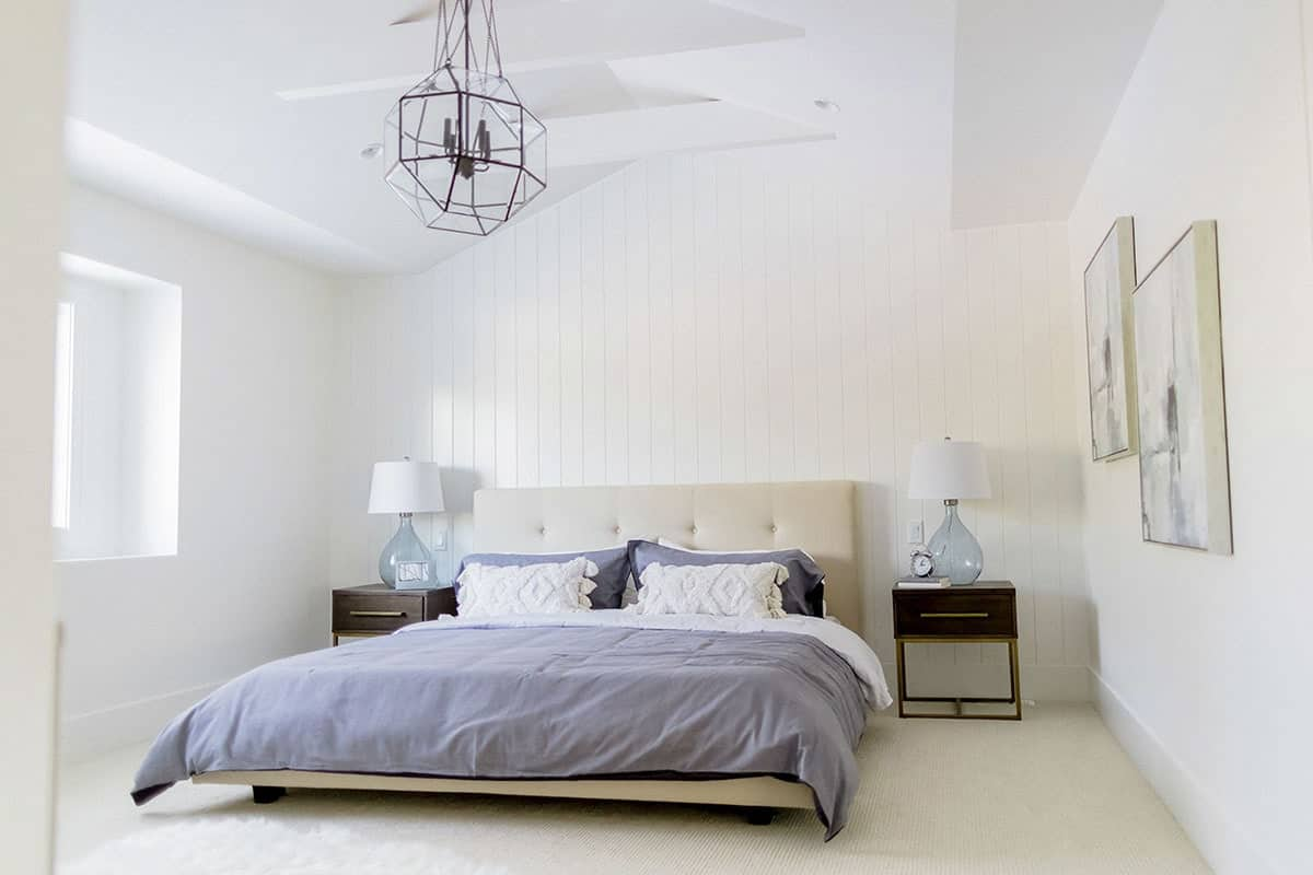 This bright master bedroom showcases a beige tufted bed and dark wood nightstands topped with glass table lamps. It is decorated with a pair of matching artworks and a geometric chandelier that hung from the vaulted ceiling.