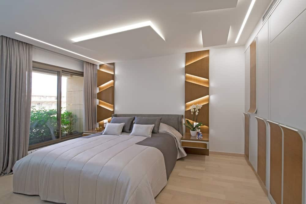 Glowing wood panels set a stunning backdrop in this primary bedroom with hardwood flooring and glass sliding windows covered in gray drapes. It features a comfy bed flanked by built-in nightstands.