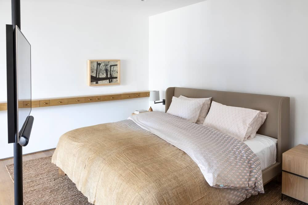This primary bedroom offers wooden nightstands and a taupe wingback bed that sit on a beige textured rug. There's a pole on the side that holds the flat-screen TV.