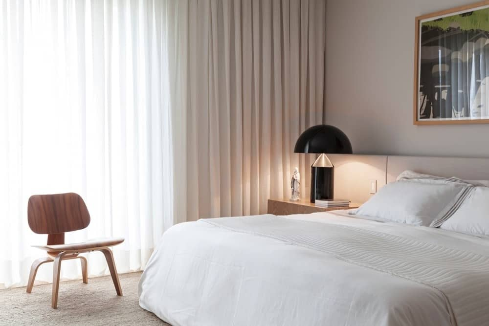 A cozy primary bedroom decorated with a stylish table lamp and an interesting artwork mounted above the white bed. It offers a wooden chair situated against the full height windows covered in sheer curtains.