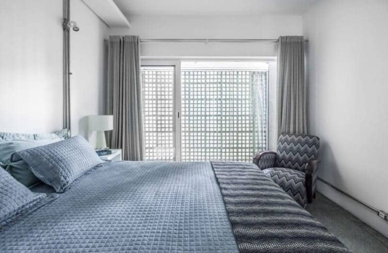 Industrial-style primary bedroom furnished with a comfy bed and a chevron armchair placed in front of the gray curtain. The room has concrete tiled flooring and plain white walls with exposed pipes.
