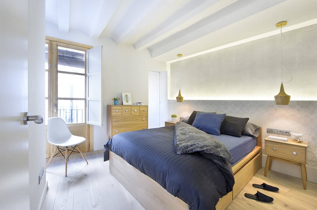 This primary bedroom showcases wooden pendants and furniture that blend in with the wide plank flooring. It has a white beamed ceiling and a french door that opens out to the balcony.