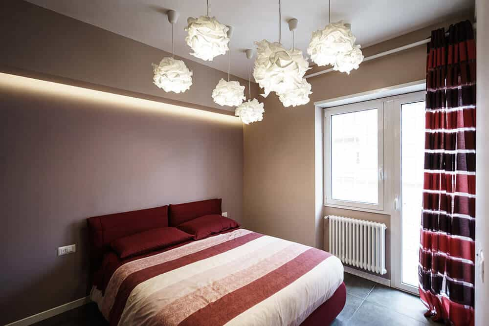 This primary bedroom is styled with unique floral lighting mounted on the white regular ceiling. It has striking drapes that complement the burgundy bed covered in a striped blanket.