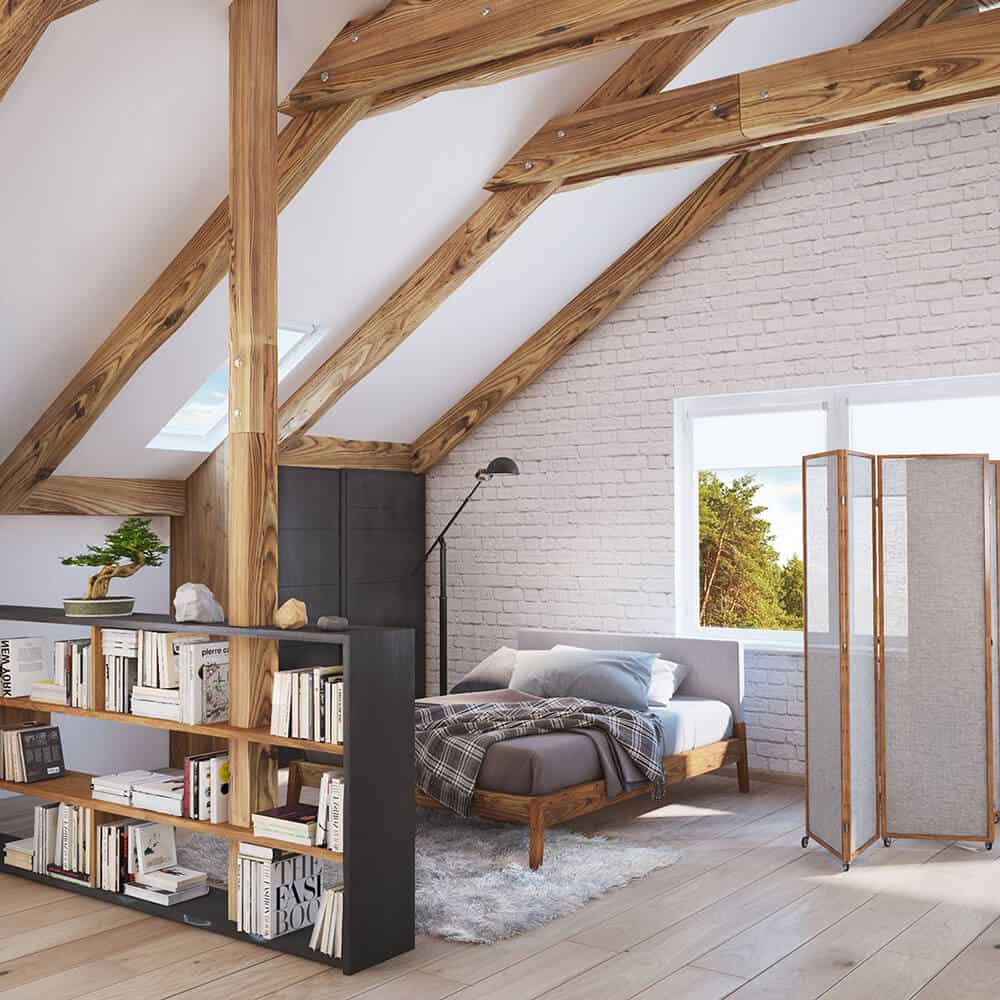 Exposed wood beams provide a sleek contrast to the vaulted ceiling and white brick walls in this primary bedroom. It has wide plank flooring and glazed windows that bring natural light in.