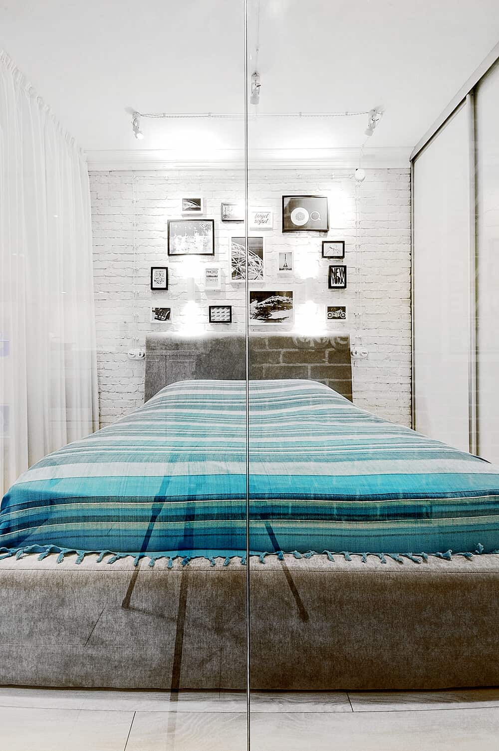 A small bedroom designed with gallery frames mounted on the white brick wall. Striped textiles stand out against the white walls and sheer curtains.