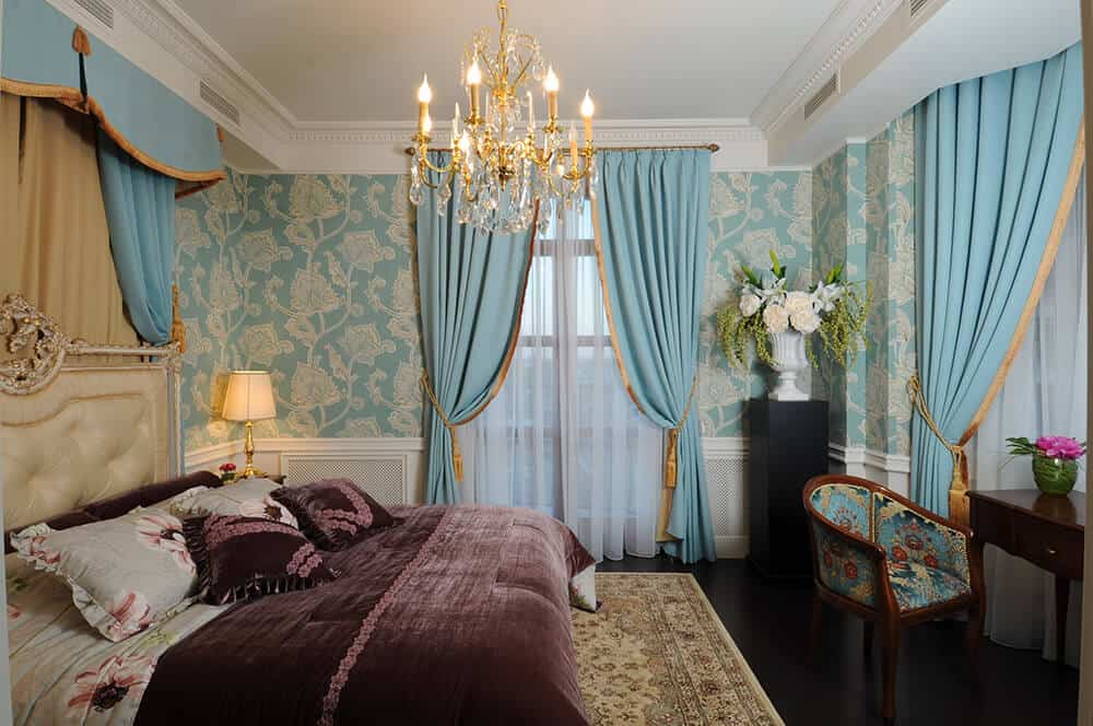 A classic master bedroom styled with gold candle chandelier and blue floral wallpaper fixed above the white wainscoting. It is furnished with a gorgeous tufted bed, a flower pedestal and a dark wood desk paired with a patterned round back chair.