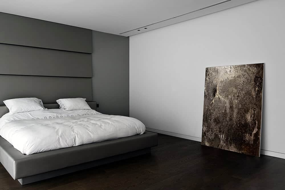 The minimalist primary bedroom features a large painting that rests against the white wall. It includes a gray platform bed sitting over the dark hardwood flooring.