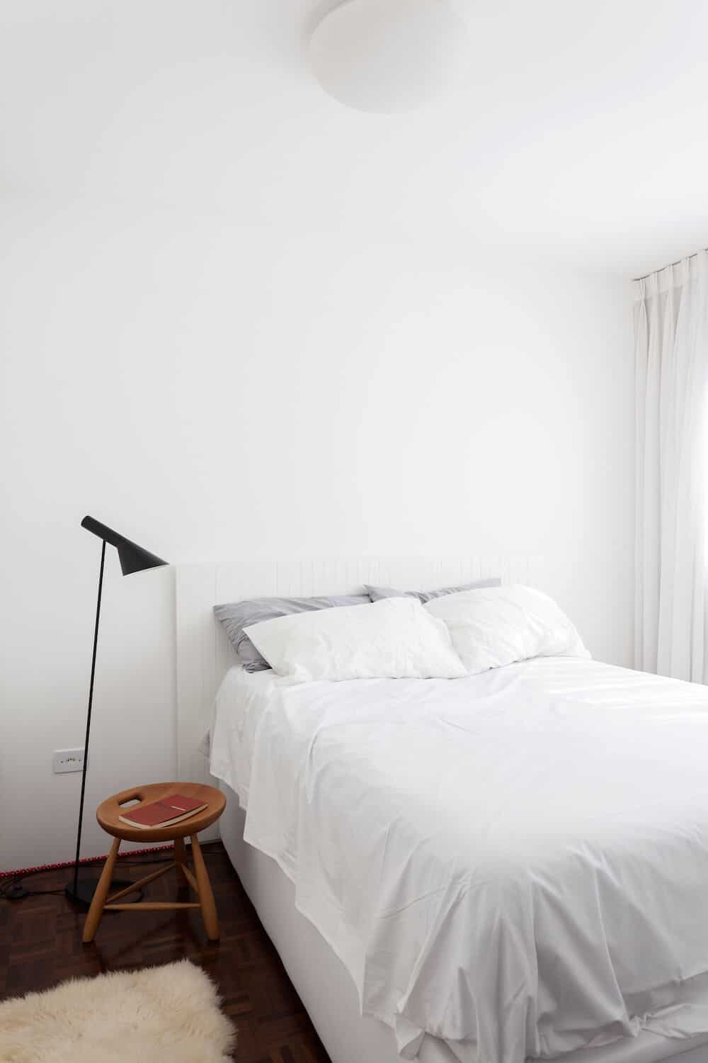 White primary bedroom contrasted by a parquet dark hardwood flooring. The room is filled with a beadboard bed, a faux fur rug and a small round side table lighted by a black floor lamp.
