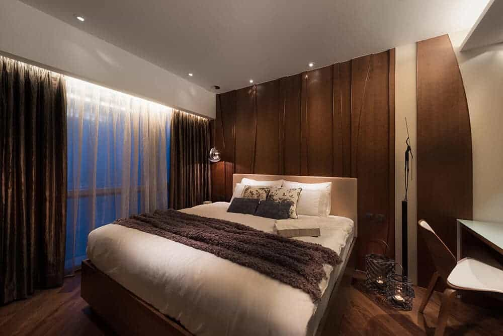 Rich wooden panels provide a cozy backdrop to the platform bed that matches the hardwood flooring. Brown and sheer curtains along with caged lamps completed the warm look.