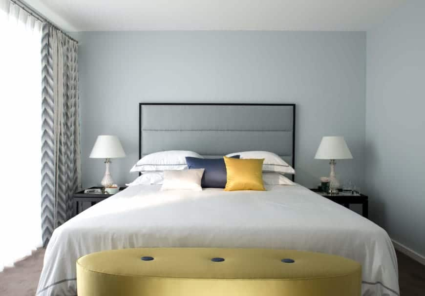 Muted blue walls brightened this primary bedroom that showcases a sleek contrast of dark hardwood flooring. Gold and blue tones from the <a class=