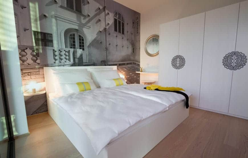 Modern primary bedroom designed with a stunning mural and decorative handles fitted on the minimalist wardrobes. Subtle yellow accents contrast the sleek white bed.