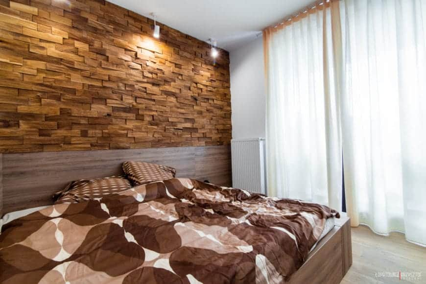 The primary bedroom features a large wood frame bed, more floor to ceiling exterior glass for natural light, and a unique wood-brick wall surface illuminated by focused light sources.