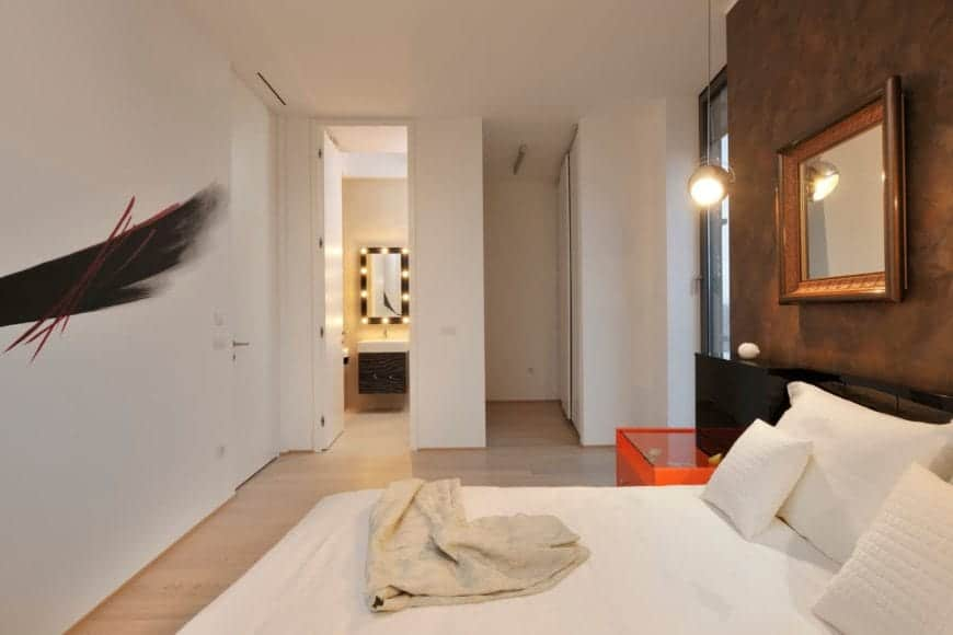 The white primary bedroom features a small private bath with an exterior glass door on right and artistic paint element on the left wall.