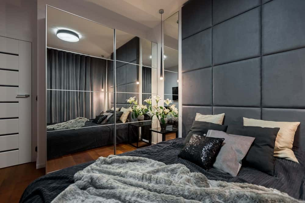 Apartment primary bedroom with rich hardwood flooring, paneled mirrors and a comfy bed with a large custom headboard.