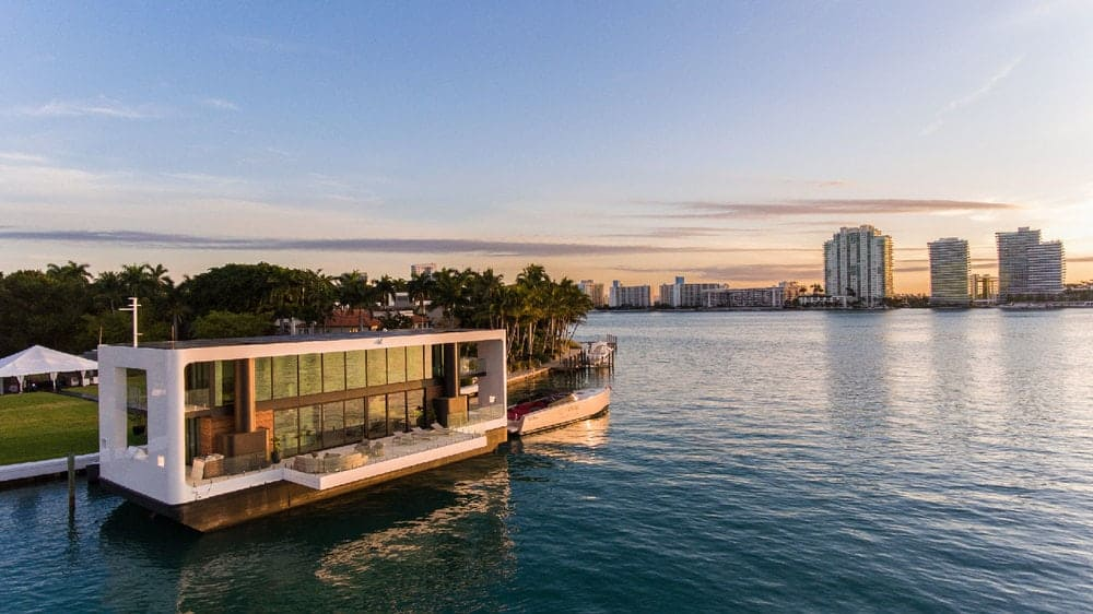 An aerial of the Arkup floating villa that is docked against a sunset sky and a beautiful view of the city skyline. Images courtesy of Toptenrealestatedeals.com.