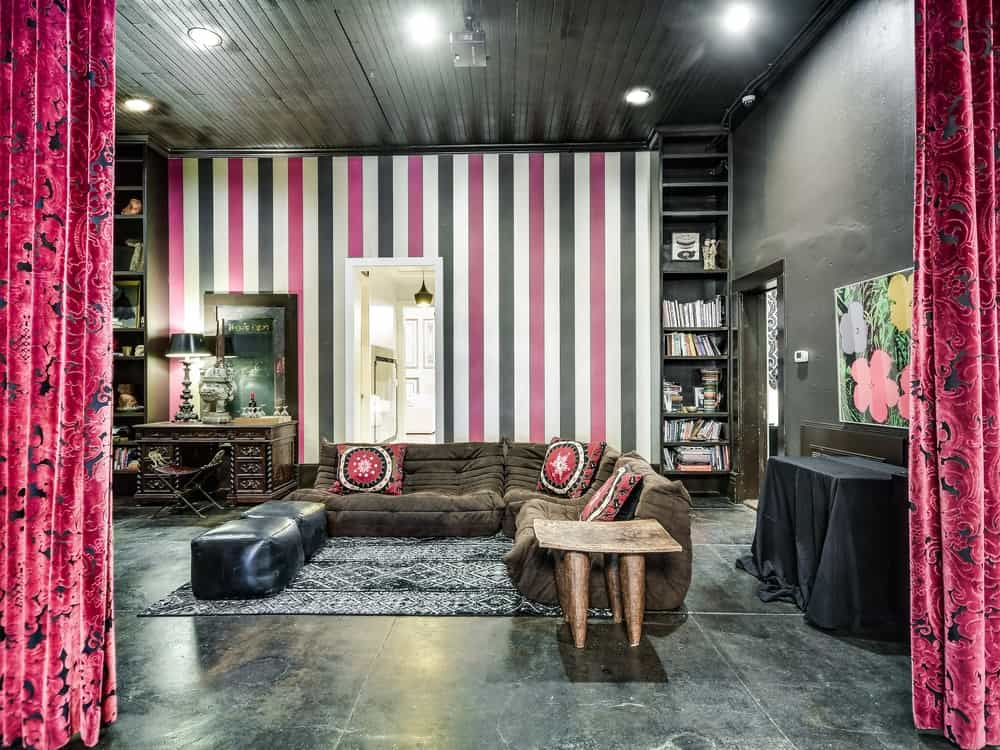 This spacious living room has black walls, ceiling and floor that makes the red elements stand out like the curtains, pillows and the red stripes of the wallpaper.