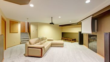 A gorgeous basement with beige walls matching with the large L-shaped beige sectional sofa in the middle of the carpeted flooring.