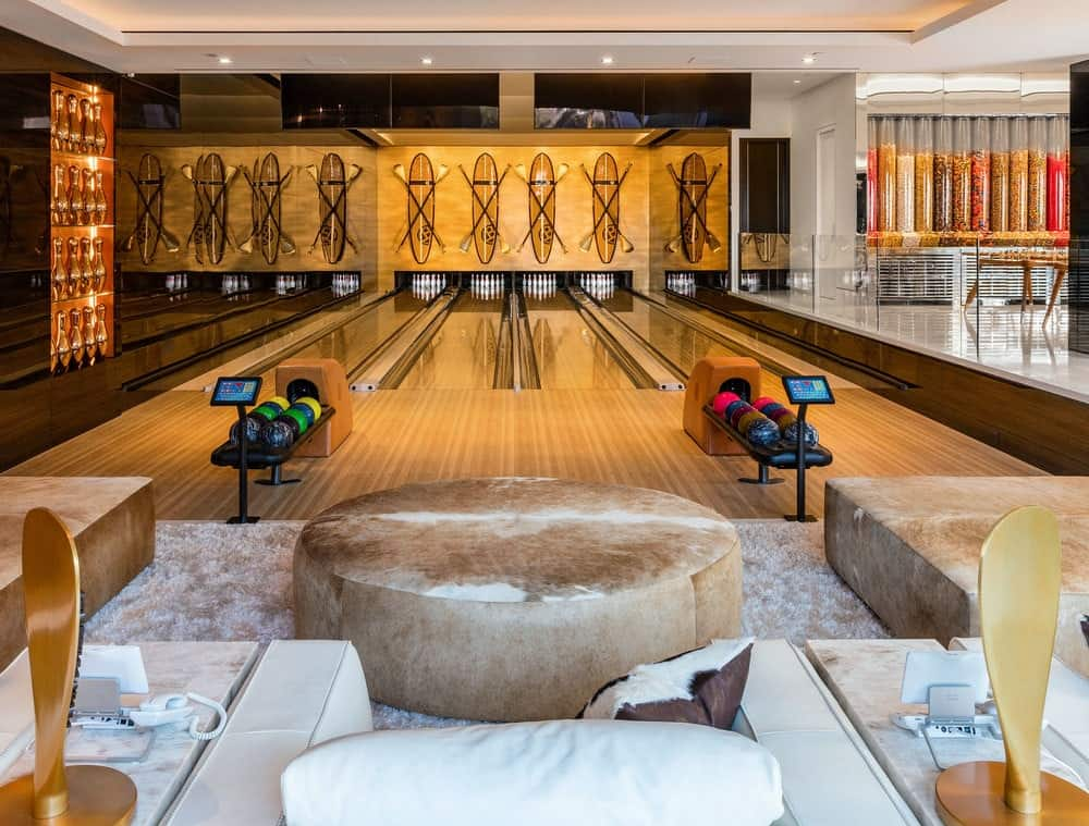 This giga mansion has its own rows of bowling alleys inside its immense game room. The bowling alley has beautiful wooden flooring with beautiful black mirrored walls and paddle board decors at the far end for a nice beach-style touch. Images courtesy of Toptenrealestatedeals.com.