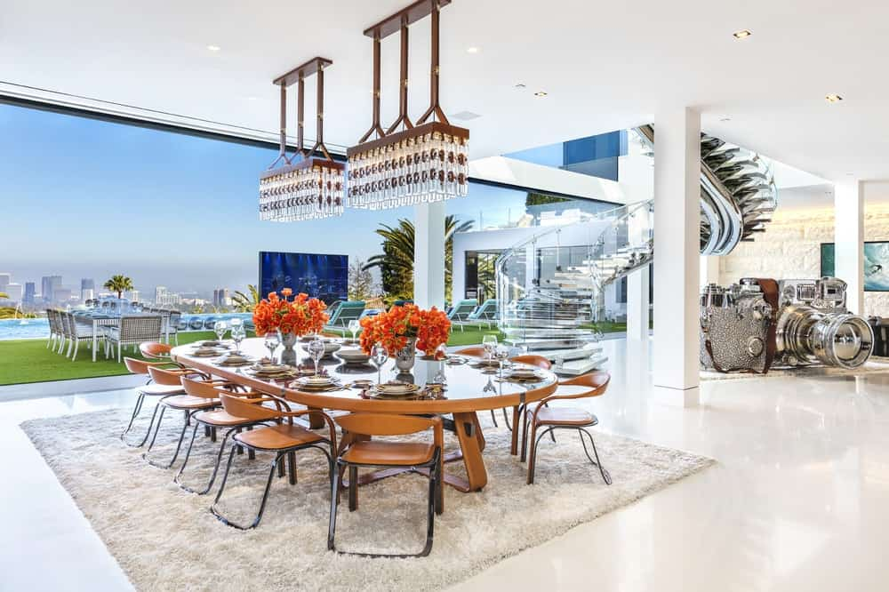 This luxurious formal dining area has a large elliptical glass-top dining table topped with a pair of crystal chandeliers and has a clear view of the backyard pool through a wide open wall. There is also a large outdoor dining area by the pool with a woven wicker dining set. The glass walls match well with the spiral glass staircase beside the dining area. Images courtesy of Toptenrealestatedeals.com.