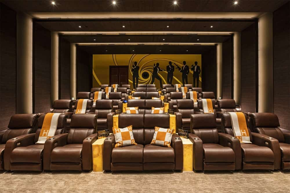 The luxurious and large entertainment room is almost a full-sized cinemahouse with several sets of dark brown leather sofas for a relaxing viewing experience. There is also a large mural of James Bond at the far wall that gives the large room character. Images courtesy of Toptenrealestatedeals.com.