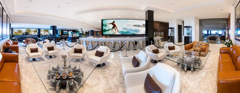 This large lounge area also houses a long luxurious bar paired with modern silver stools and a large wide-screen TV perfect for sporting events. On the far end, you can see a part of the luxury car collection parked for display before a glass wall. Images courtesy of Toptenrealestatedeals.com.