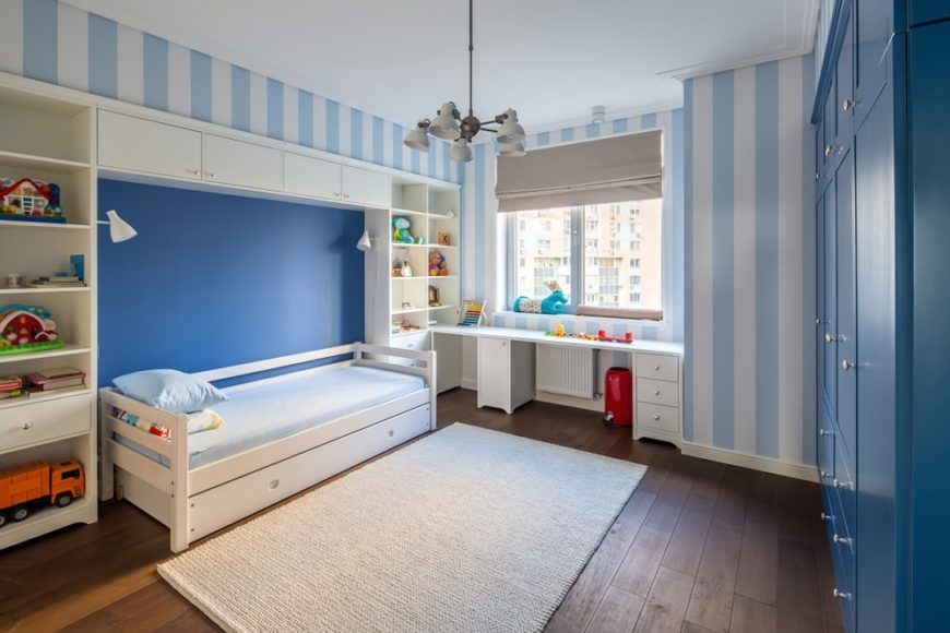 A charming kid's bedroom with blue-striped walls and hardwood flooring.