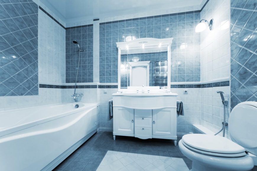 A beautiful primary bathroom with blue tiles on the walls and flooring.