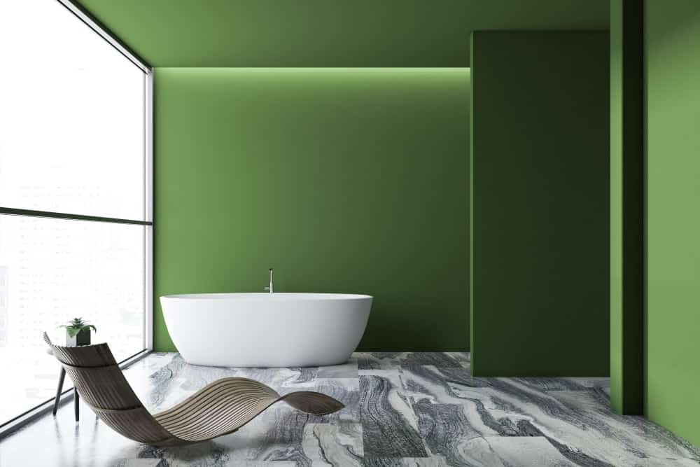 A spacious and bright bathroom with green walls.