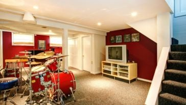 A cool basement with a drum set and red walls.