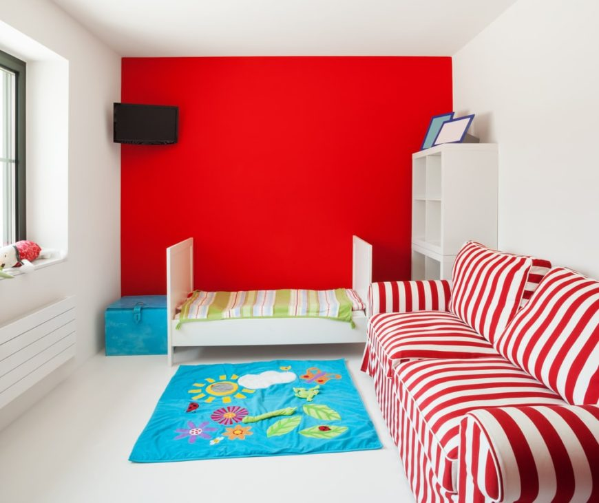 A simple yet dynamic kid's bedroom with a red wall and red-striped sofa.