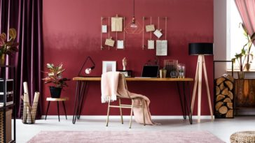 A charming home office with a cozy feel and red wall.